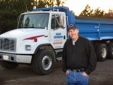 Braun Excavating, LLC - Owner / Operator Doug Braun standing in-front of the company's white and blue dump truck